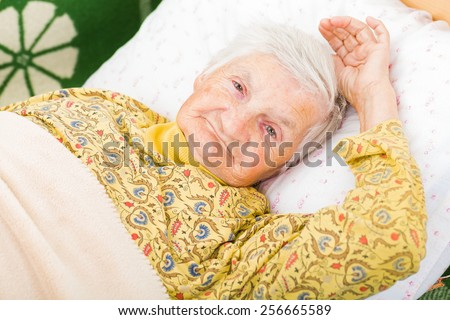 Sweet smiling elderly woman resting in bed