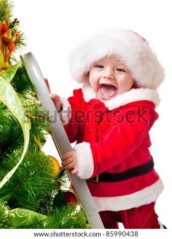 Sweet smiling toddler in Santa hat decorating Christmas tree