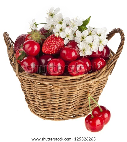 Sweet strawberry and cherries with flowers in basket isolated on white background