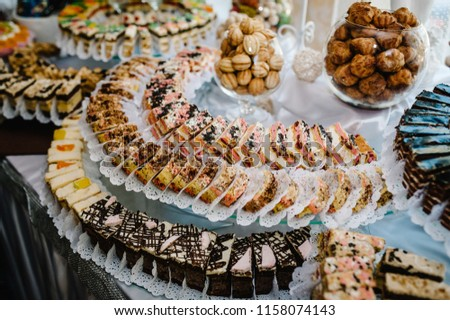 Sweet table. A plates of cakes and muffins with cream with berries. Table with sweets, candy, buffet. Dessert table for a party goodies. Close up. party reception, decorated in restaurant. candy bar
