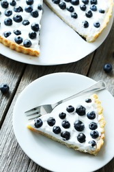 Sweet tart cake with blueberries on grey wooden background