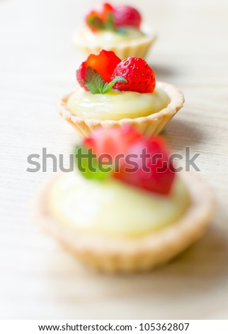 stock photo : Sweet tartelettes filled with vanilla cream and strawberries