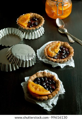 Sweet tartlets with fruit jelly and orange on black table