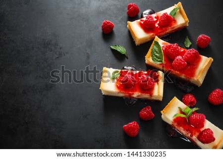 Sweet tasty background. Tasty cheese cake served with sauce, mint and raspberry on dark background. Copy space. Horizontal.  #1441330235