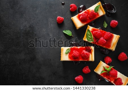 Sweet tasty background. Tasty cheese cake served with sauce, mint and raspberry on dark background. Copy space. Horizontal.  #1441330238