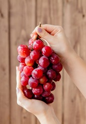 Sweet tasty grapes in graceful woman's hand on wooden background, copy space.