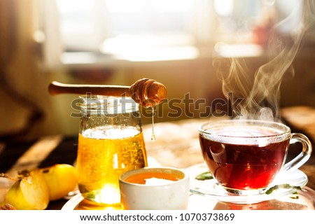 Sweet tea with lemon and honey close-up. a healthy drink. Close-up honey dipper and bowl full of bee honey.