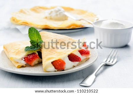 Sweet thin french style crepes folded with strawberries and cream