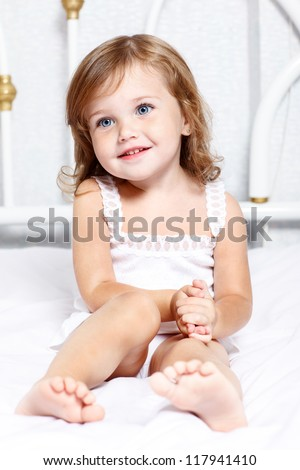 Sweet thoughtful little girl sits in bed
