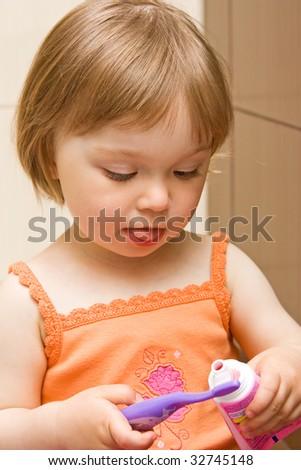 sweet toddler baby girl cleaning teeth