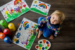 Sweet toddler blond child, boy, painting with colors, making finger prints on the paper