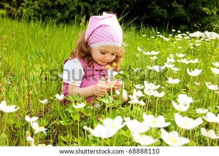 Sweet toddler girl examining white flowers