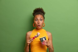 Sweet tooth and temptation concept. Speechless surprised Afro American woman eats tasty cold dessert, enjoys ice cream with strawberry flavor, dressed in yellow summer clothes, green background