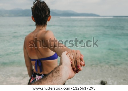 Sweet tourist woman holding hands with her boyfriend in Gili Trawangan island, Indonesia on a beautiful beach with the blue sea backgrounds. Lifestyle. Travel photography.
