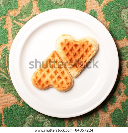 sweet wafer heart on dish, on retro background