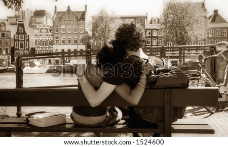sweet young couple sitting on a bench and hugging