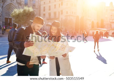 Sweet young couple using the map in Barcelona center Stylish hipster girl with her boyfriend using touristic guide during walk in historic center of the city.Young couple in love spend their honeymoon
