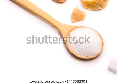 Sweetener made from sugarcane,​ Granulated sugar in a wooden spoon on white background.