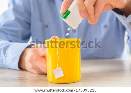 Sweetener tablets and hand with box whit cup of tea