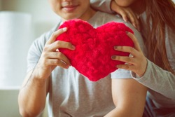 Sweetheart young couple embracing together while holding red heart in their hands at living room. Hands of young happy couple hold red heart cloth symbol love. Valentine day concept.