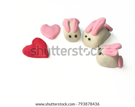 Sweetie color clay plasticine made are beautiful rabbits family and lovely hearts placed on white background, cute animal dough #793878436