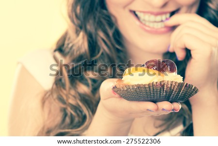 Stock Photo Sweetness and happiness concept. Closeup cute flirty woman eating fruit cake licks fingers