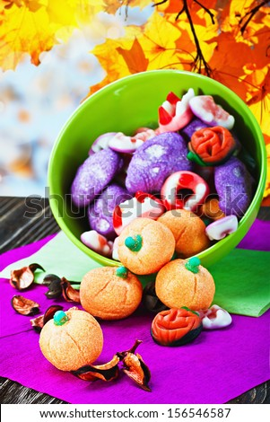 sweets and candies for the holiday halloween on a background of leaves and sky