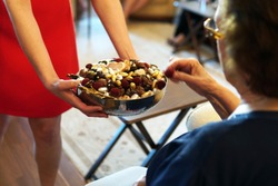 sweets like confectionery and chocolates served by a girl, dressed red, to elder people, a traditional ceremony for ramadan feast or sacrifice feast known as eid al-adha