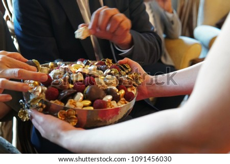 sweets like confectionery and chocolates served by a girl, dressed red, to elder people, a traditional ceremony for ramadan feast or sacrifice feast known as eid al-adha #1091456030