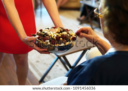 sweets like confectionery and chocolates served by a girl, dressed red, to elder people, a traditional ceremony for ramadan feast or sacrifice feast known as eid al-adha #1091456036