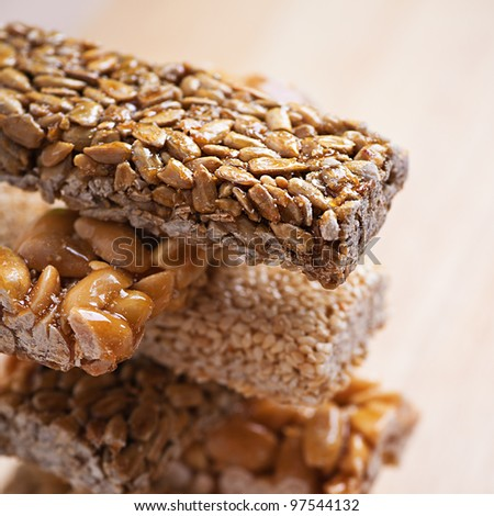 sweets piled tower (kozinaki, candied roasted nuts, peanuts and hazelnuts in icing sugar) on wooden background