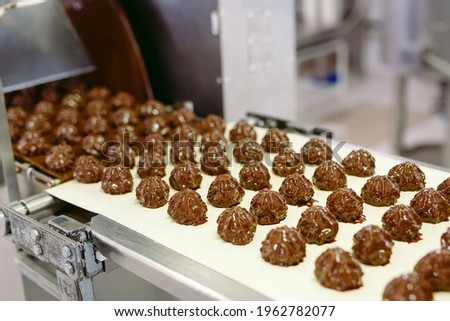 sweets production and industry concept - chocolate candies processing on conveyor at confectionery shop
