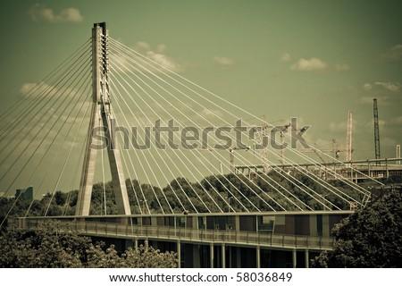 Swietokrzyski bridge on Vistula river in Warsaw. With cranes on construction site of National Stadium in background. Retro style.