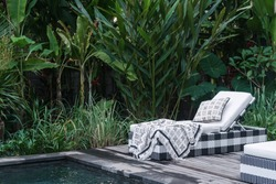 Swim pool with plaid and pillow on comfortable rattan deckchairs standing on territory of luxurious spa resort and recreation villa against natural plants on green leafy background