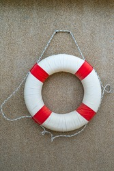 Swim ring or life preserver for safety that hang on the sandwash wall at the beach.