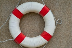 Swim ring or life preserver that hang on the sandwash wall at the beach.
