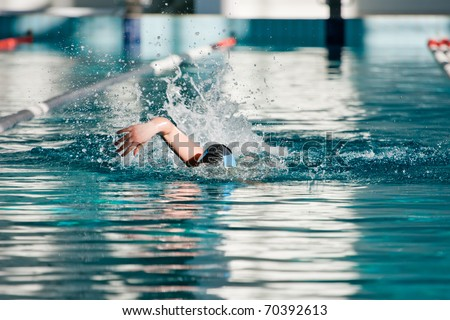 Swimmer athlete with splashes of swims in the pool