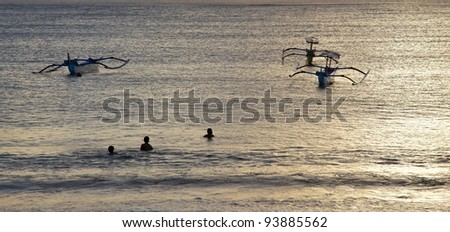 Swimmers and traditional jukungs (outrigger canoes), Tuban Beach, Bali, Indonesia.