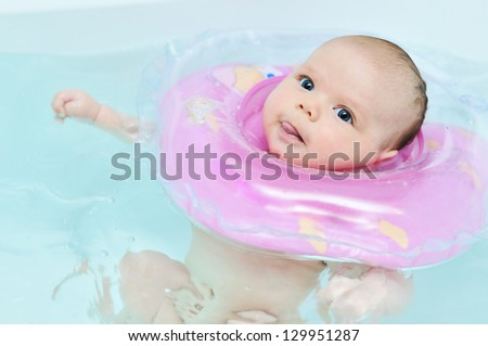 swimming baby in the bath  showing tongue