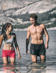 Swimming couple of swimmers having fun in cold water lake for winter polar plunge challenge outdoors. Laughing Asian woman in sports clothing and young man walking out of freezing temperature river.