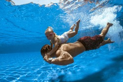 Swimming family, father and child in water, pool