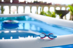Swimming goggles are on the rubber pool.