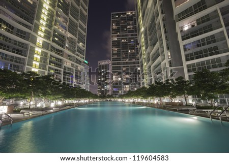 Swimming pool among high rise buildings by night