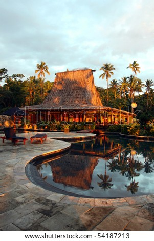 Swimming pool and bar-hut in tropical resort.  Beautiful sunset