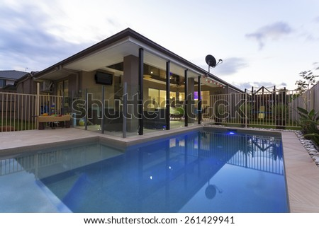 Swimming pool and outdoor entertaining area in stylish home at dusk