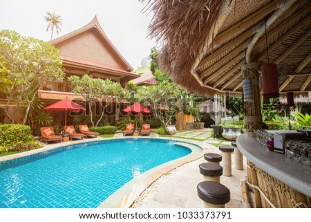 Swimming pool area with bar in luxury hotel resort. Hot summer day, holiday and travel in asia #1033373791