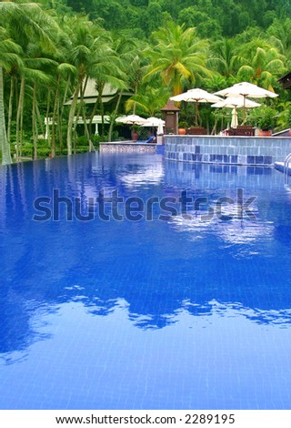 Swimming pool at a resort with blue water reflecting coconut palm trees. Water ripple not noise.