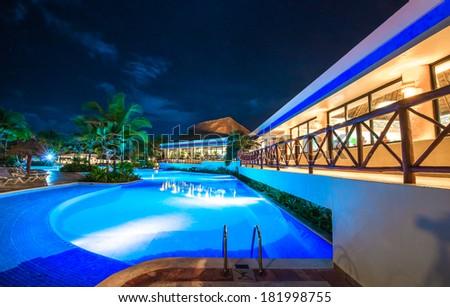 Swimming pool at promenade and restaurant at luxury caribbean resort at night, dawn time. Bahia Principe, Riviera Maya, Mexico.