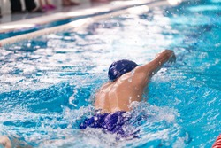 Swimming pool athlete training indoors for professional competition. Teenager swimmer doing free style