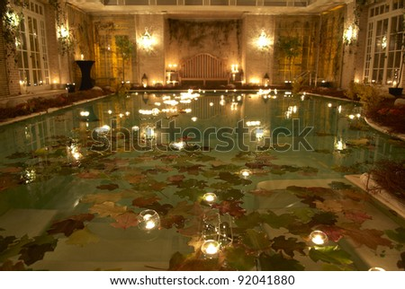 Swimming pool by night. Decoration with candle.